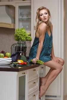 ランジェリーのセクシーな女性は台所のテーブルに座っています