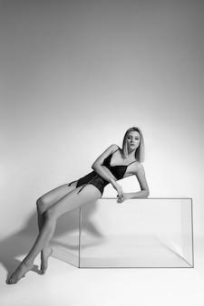 Сексуальная женщина в нижнем белье нижнего белья лежит на стеклянном кубе. обнаженная сексуальная женщина в нижнем белье с длинными ногами. идеальная фигура, стройное тело. страстная взрослая обнаженная девушка в нижнем белье