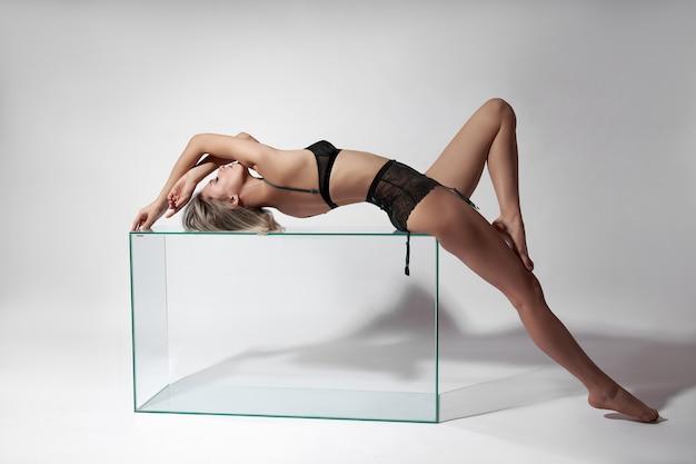 란제리 속옷에 섹시한 여자는 유리 큐브에 누워있다. 긴 다리와 란제리 누드 섹시 한 여자.