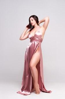 灰色の背景、フルレングスの肖像画のスタジオで深いネックラインとピンクのドレスのセクシーな女性