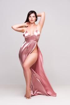 회색 벽, 전체 길이 초상화에 깊은 목선과 핑크 드레스에 섹시한 여자