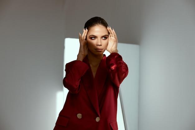 赤いジャケットのセクシーな女性は彼女の顔に触れます