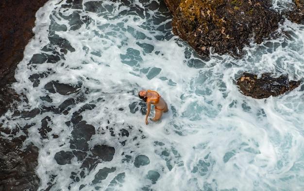 波の近くの海でセクシーな女性。上面図、空中射撃。