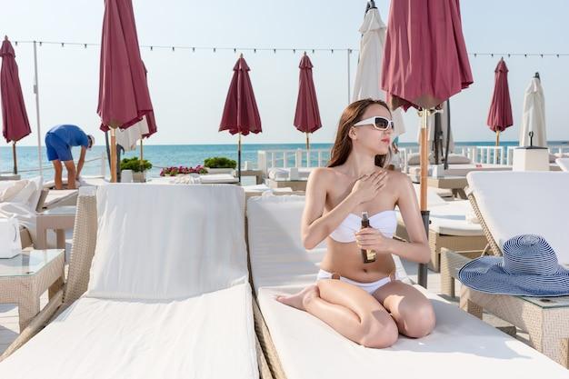 Сексуальная женщина в летнем пляжном наряде сидит на шезлонге и наносит солнцезащитный лосьон на свое тело, глядя вдаль.