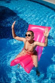 선글라스를 끼고 수영장에 있는 분홍색 매트리스에서 휴식을 취하고 일광욕을 하는 섹시한 여자. 풍선 핑크 매트리스에 떠 있는 베이지색 비키니 수영복에 젊은 여자