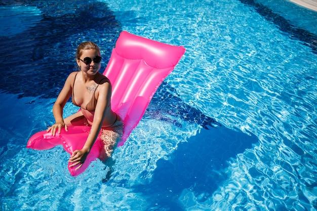 プールのピンクのマットレスで休んで日光浴をしているサングラスのセクシーな女性。インフレータブルピンクのマットレスに浮かぶベージュのビキニ水着の若い女性