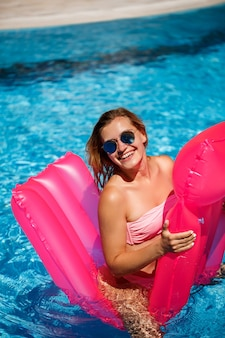 水着姿で笑顔のサングラスをかけたセクシーな女性は、プールのピンクのインフレータブルマットレスの上に横たわっています。暑い夏の晴れた日には、プールサイドでおくつろぎください。休暇の概念