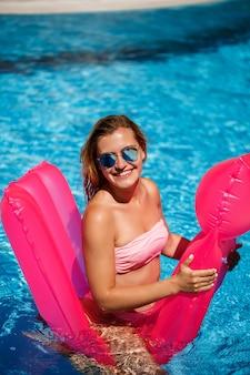 Сексуальная женщина в солнечных очках с улыбкой на лице в купальнике лежит на розовом надувном матрасе в бассейне. расслабьтесь у бассейна в жаркий летний солнечный день. концепция отпуска