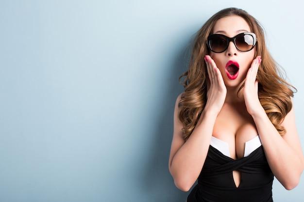 驚きのクローズアップの表情でサングラスでセクシーな女性。