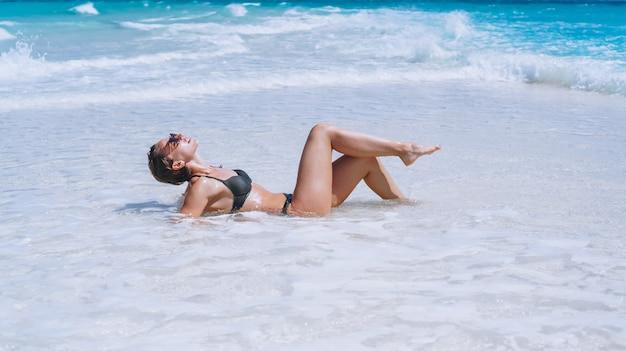 Сексуальная женщина в купальных костюмах, лежа в океане