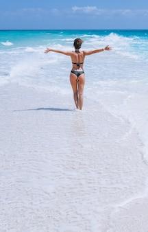 Сексуальная женщина в купальных костюмах стоит в океане