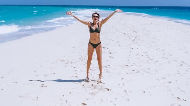 Сексуальная женщина в купальных костюмах стоит на песке у океана