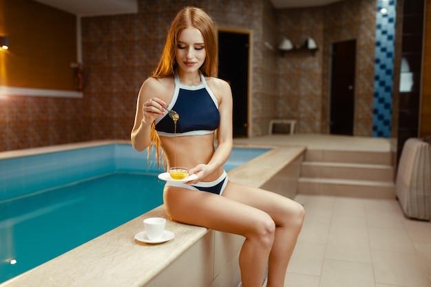 水着姿のセクシーな女性が室内のプールでお茶に蜂蜜を追加します。