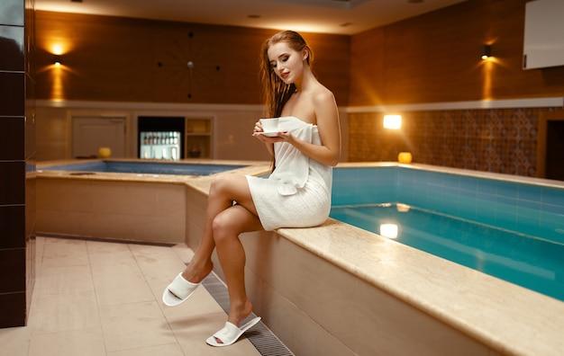 Сексуальная женщина в полотенце на теле пьет чай у бассейна в помещении.