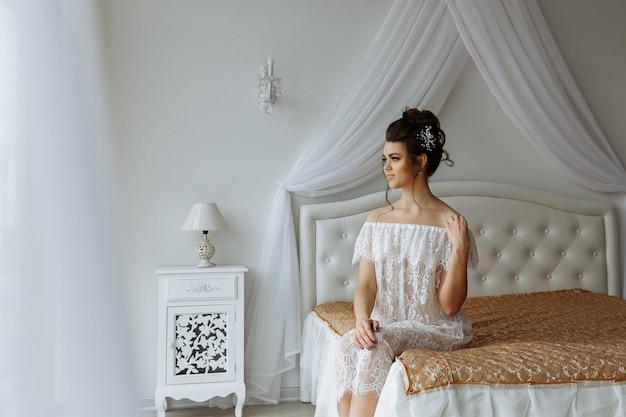 Сексуальная женщина в прозрачном нижнем белье, сидя на кровати, роскошный интерьер спальни на фоне