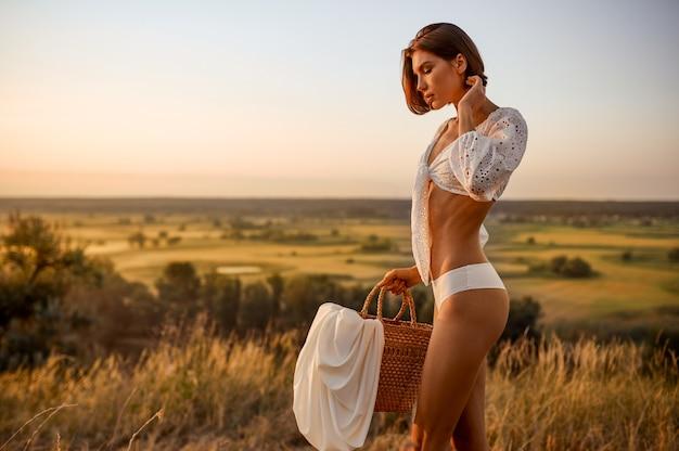 白いランジェリーのセクシーな女性は、フィールドでバスケットを保持します。日没の牧草地で下着レジャーでスリムなボディを持つ女性