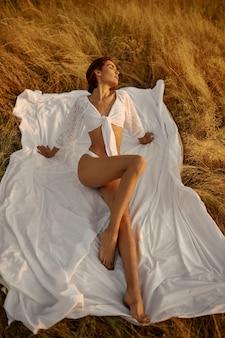 フィールドで毛布の上に座っている白いランジェリーのセクシーな女性。牧草地でのレジャー、日没時のリラクゼーション、敏感な下着でスリムなボディを持つ女性