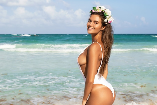 흰색 수영복에 섹시 한 여자는 해변에서 포즈