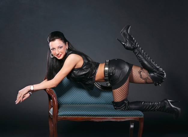 Sexy woman in leather clothing on a chair