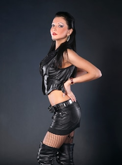 Sexy woman in leather clothing on a gray background