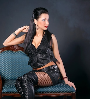 Sexy woman in leather clothing sitting on a chair