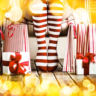Sexy woman legs with gift boxes and shopping bags