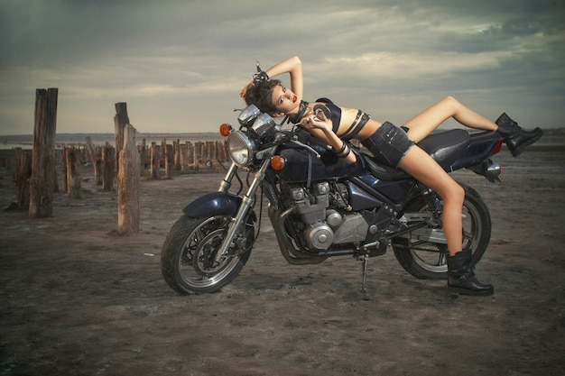 Sexy woman lies on a motorcycle