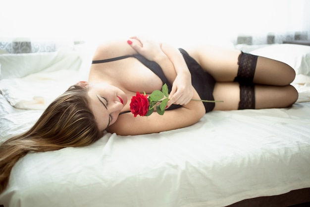 Sexy woman in lingerie lying in bed and smelling flower