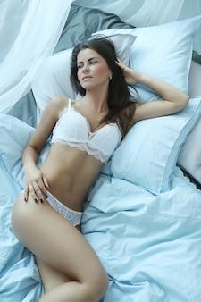 Donna sexy in lingerie sdraiata sul letto