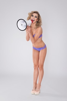 Sexy woman in lingerie screaming by megaphone