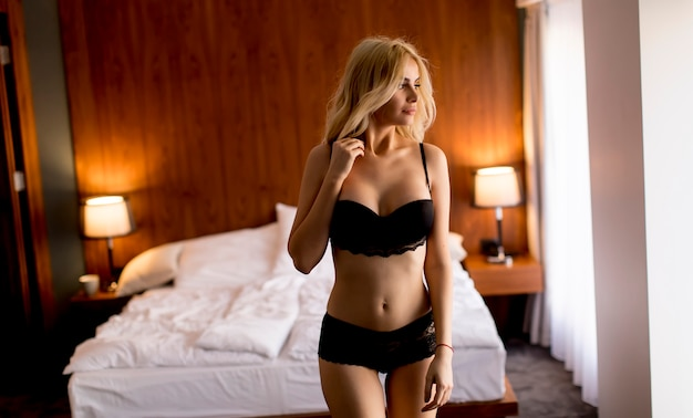 Sexy woman in lingerie standing in the bedroom