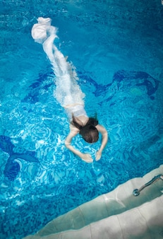 Sexy woman in long white dress diving underwater at swimming pool