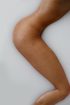 ミルクとお風呂で横になっているセクシーな女性、脚のビュー。バスタブの女性、スパの美容とヘルスケア、バスルームのウェルネストリートメント