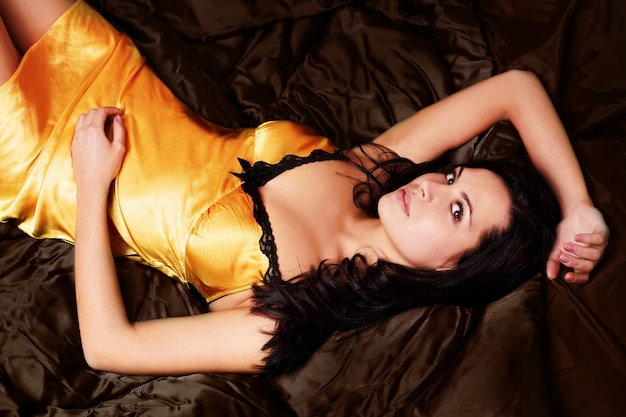Sexy woman lying on red silk sheets