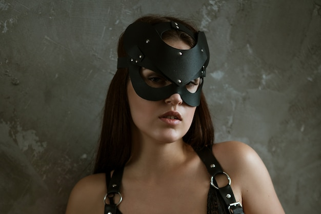 Sexy woman in a mask and black bodysuit