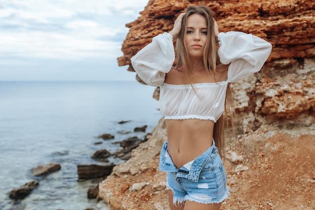 最小のショートパンツと白いブラウスで岩のビーチでセクシーな女性