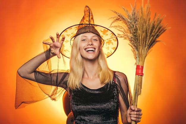 オレンジ色の背景にセクシーな女性。ハロウィーンのために飾られた背景。幸せなハロウィーン。ハロウィーン