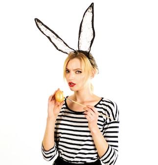 Сексуальная женщина картина яйцо. охота за яйцами. девушка пасхи в маске зайчика с покрашенными яичками.