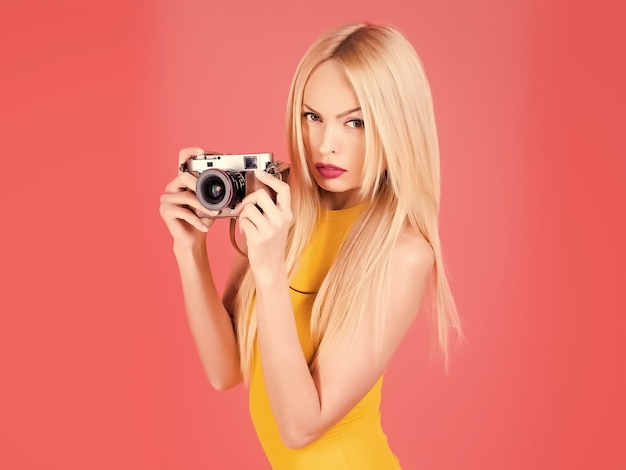 Sexy woman photographer hold camera isolated on pink Premium Photo
