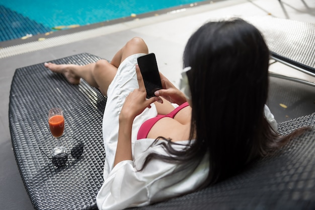 Sexy woman play smartphone at pool