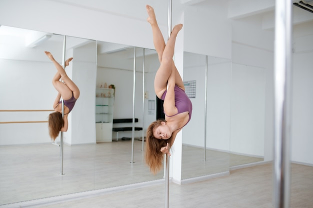 Sexy woman on pole-dancing workout in class. professional female dancers exercising in gym, pole dance