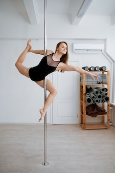 Sexy woman on pole-dancing workout in class