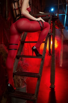 Sexy woman poses in red bdsm suit, back view, abandoned factory interior. young girl in erotic underwear, sex fetish, sexual fantasy