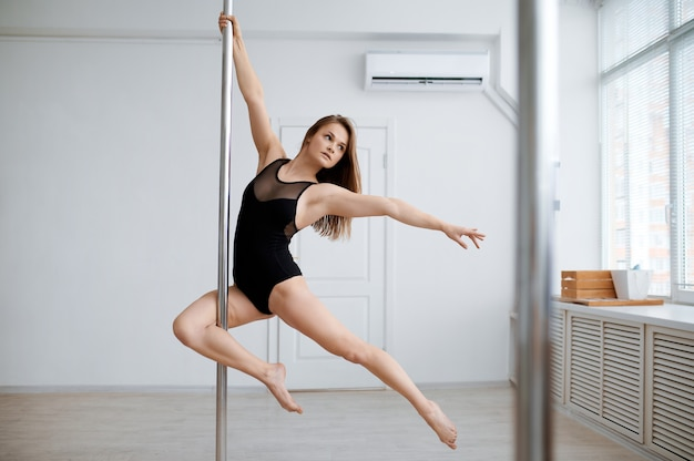 Sexy woman practice pole dance, workout in class. professional female dancers exercising in gym, pole-dancing.