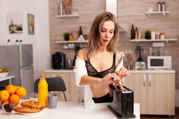 란제리에 집 부엌에서 구운 빵을 준비 하는 섹시 한 여자. 문신이 있는 섹시하고 매혹적인 젊은 여성이 건강하고 천연 수제 오렌지 주스를 마시고 상쾌한 일요일 아침을 맞이합니다.