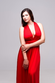 Sexy woman in red dress with deep neckline  on gray wall,
