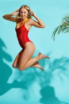 Sexy woman in red swimsuit and headphones jumping on blue