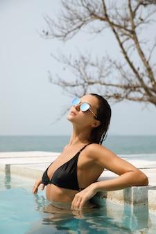 彼女の夏休みの間にプールでリラックスするセクシーな女性