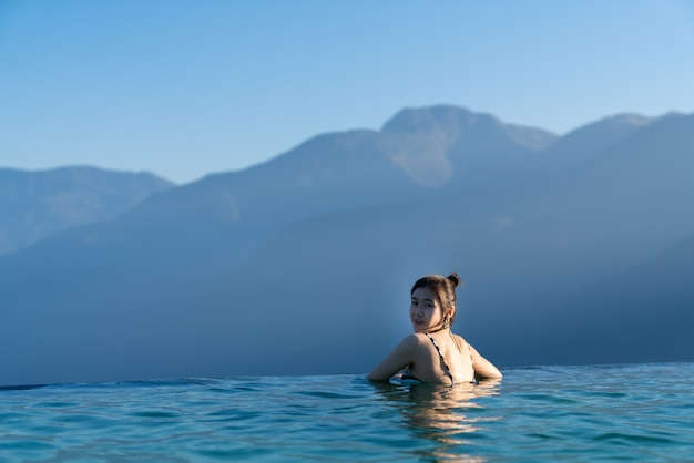 Sexy woman relaxing in infinity swimming pool   with stunning mountain view at  luxurious resort / vacation concept