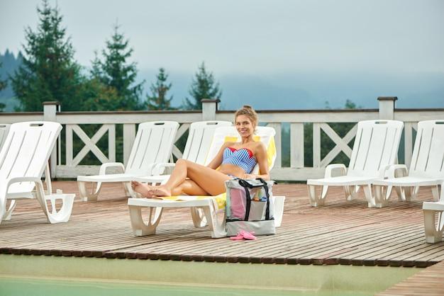 Сексуальная женщина отдыхает на шезлонге, загорая возле бассейна.